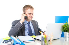 Young happy businessman smiling confident talking on mobile phone at office computer desk Royalty Free Stock Photo