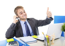 Young happy businessman smiling confident talking on mobile phone at office computer desk. Young Caucasian attractive businessman smiling confident talking on Royalty Free Stock Photos