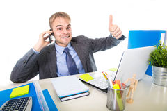 Young happy businessman smiling confident talking on mobile phone at office computer desk Royalty Free Stock Photography