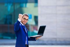 Young happy businessman standing on office building background w royalty free stock image
