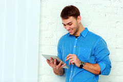 Young happy businessman standing with tablet computer near the wall Royalty Free Stock Photography