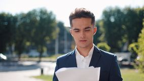 Young happy businessman in a stylish suit carefully examines the papers outdoor. Successful lifestyle, contract stock video
