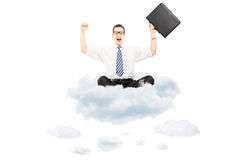 Young happy businessman with suitcase riding on clouds Stock Image