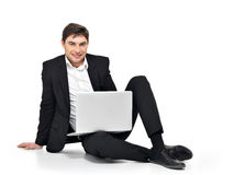 Young happy businessman working on laptop Stock Images