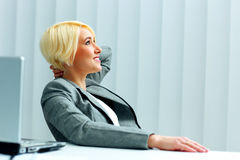 Young happy businesswoman in gray jacket looking up Stock Photography