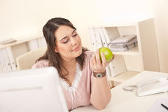 Young happy businesswoman holding apple at office Royalty Free Stock Photo