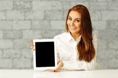 Young happy businesswoman showing tablet computer Stock Image