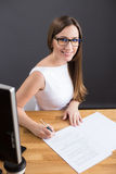 Young happy businesswoman signs contract in office Stock Images