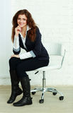 Young happy businesswoman sitting on a chair near the wall Royalty Free Stock Photo