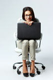 Young happy businesswoman sitting with laptop Stock Image