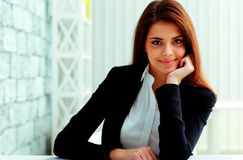 Young happy businesswoman sitting at the table on her workplace Royalty Free Stock Photos