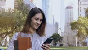 Young happy businesswoman standing in financial district of New York, USA and using the smartphone as mobile office. stock footage