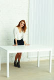 Young happy businesswoman standing near the table Stock Photo