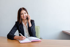 Young happy businesswoman talking on the phone and writing notes in office royalty free stock photos