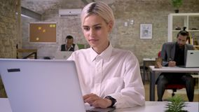 Young happy businesswoman is typing on laptop in office, colleagues are networking with technologies, work concept. Communication concept stock footage