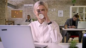 Young happy businesswoman is typing on laptop in office, drinking coffee, colleagues are networking with technologies. Work concept, communication concept stock footage
