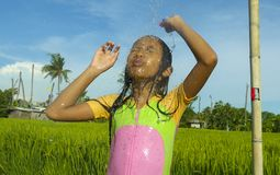 Young happy and carefree beautiful child 7 or 8 years old outdoors having shower at a beautiful rice terrace playful under the. Water wearing cute girl swimsuit stock images