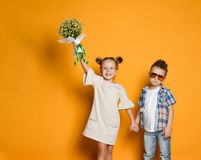 Young happy caucasian boy gives a flowers to his girlfriend isolated over yellow background. Little girl is happy to receive a bouquet of daisies from her stock images