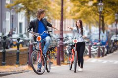 Young happy caucasian couple on bikes in old streets in Amsterdam. Young happy ouple on bikes in old streets in Amsterdam Stock Images