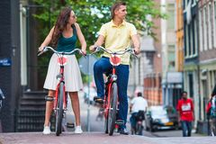 Young happy caucasian couple on bikes in old streets in Amsterdam. Young happy ouple on bikes in old streets in Amsterdam Royalty Free Stock Images