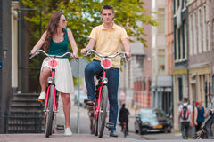 Young happy caucasian couple on bikes in old streets in Amsterdam Royalty Free Stock Photography