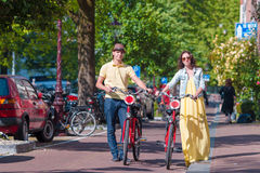 Young happy caucasian couple on bikes in old streets in Amsterdam Stock Photo