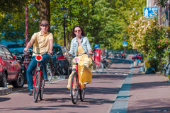 Young happy caucasian couple on bikes in old streets in Amsterdam Stock Photos