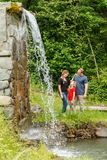 Young happy Caucasian family of father, mother and daughter stand together in sunny summer mountain forest near waterfall. Young happy Caucasian family of father royalty free stock photo