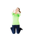 Young happy caucasian woman jumping in the air with thumbs up Stock Photos