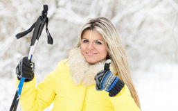 Young happy caucasian woman with ski poles at winter outdoor Royalty Free Stock Images