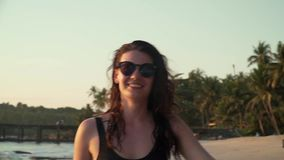 Happy woman enjoys vacation on the beach at sunset stock video