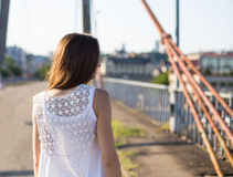Young happy caucasian woman walkong on old bridge in city park outdoor. Relax lifestyle summer concept. Young happy caucasian woman walkong on old bridge in city Stock Photo