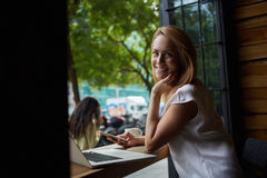 Young happy charming female posing while holding mobile phone, attractive woman relaxing after work on laptop computer while sitti Royalty Free Stock Photo