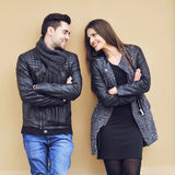 Young happy cheerful couple standing near a wall and looking to Royalty Free Stock Images