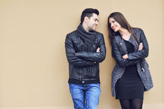 Young happy cheerful couple standing near a wall and looking to Stock Images