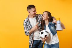 Young happy cheerful couple supporter, woman man, football fans cheer up support team, holding megaphone, soccer ball. Young happy cheerful couple supporter royalty free stock images