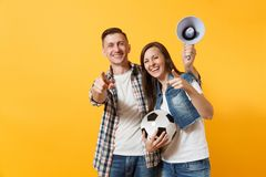 Young happy cheerful couple supporter, woman man, football fans cheer up support team, holding megaphone, soccer ball. Young happy cheerful couple supporter stock photo