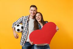 Young happy cheerful couple supporter, woman man, football fans cheer up support team, holding red heart love, soccer. Young happy cheerful couple supporter stock photo