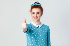 Young happy cheerful redhead girl showing thumb up and toothy smile.  studio shot on gray background. Young happy cheerful redhead girl showing thumb up and Stock Photography