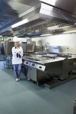 Young happy chef standing next to work surface. In professional kitchen royalty free stock photos