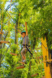 Young happy child boy in adventure park in safety equipment Royalty Free Stock Image