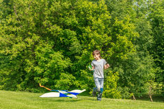 Young happy child boy playing with bright kite in park Royalty Free Stock Photo