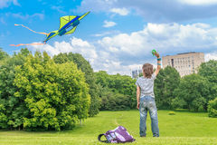 Young happy child boy playing with bright kite in park Stock Photos