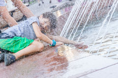 Young happy child boy playing with water fountain Stock Photo