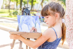 Young happy child girl drawing a picture outdoors Stock Photo