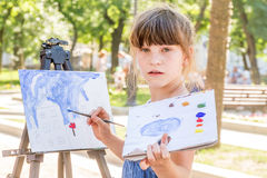 Young happy child girl drawing a picture outdoors Royalty Free Stock Images