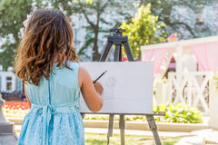Young happy child girl drawing a picture outdoors. Kid painting stock image