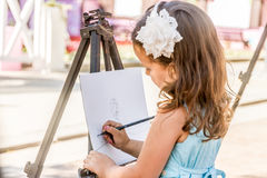 Young happy child girl drawing a picture outdoors. Kid painting royalty free stock photography