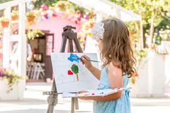 Young happy child girl drawing a picture outdoors. Kid painting stock photos