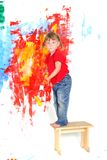 Young happy child girl painting white wall Royalty Free Stock Images